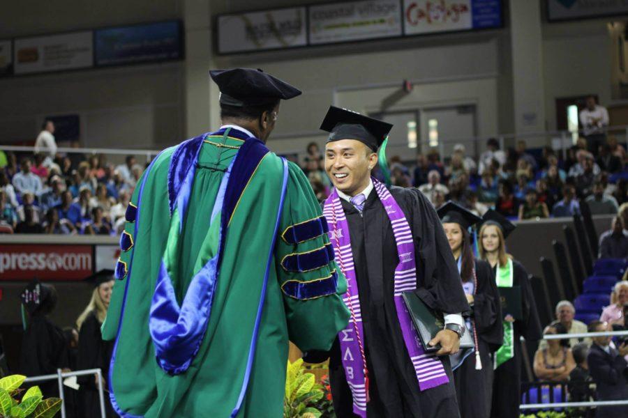 Nosaj Lesrosa shakes FGCU President Dr. Wilson Bradshaw during the Spring 2015 Commencement ceremony at Alico Arena. (EN Photo / Kelli Krebs)