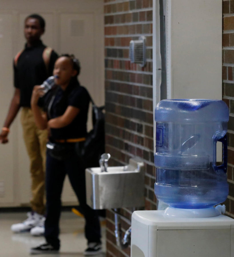 Students walk by a water fountain and water cooler at Noble School in Detroit, Tuesday, Sept. 4, 2018. Some 50,000 Detroit public school students will start the school year Tuesday by drinking water from coolers, not fountains, after the discovery of elevated levels of lead or copper — the latest setback in a state already dealing with the consequences of contaminated tap water in Flint and other communities. (AP Photo/Paul Sancya)