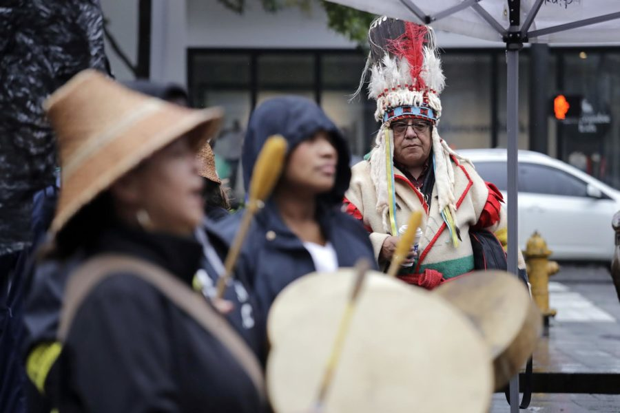Leon Rattler, right, a member of the Blackfeet Nation, looks on as women drum during an Indigenous Peoples Day blessing and rally before a march Monday, Oct. 8, 2018, in Seattle. In 2014, the Seattle City Council voted to stop recognizing Columbus Day and instead turned the second Monday in October into a day of recognition of Native American cultures and peoples. (AP Photo/Elaine Thompson)