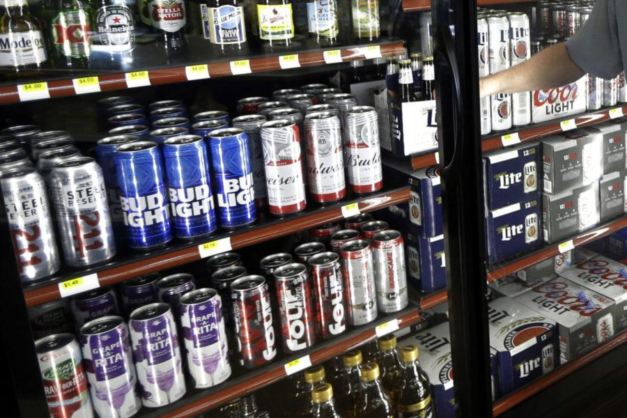 """FILE - This Wednesday, April 19, 2017 file photo shows the beer cooler behind the counter in a convenience store in Sheridan, Ind. In future sweltering years with a double whammy of heat and drought, losses of barley yield can be as much as 17 percent, computer simulations show. And that means """"beer prices would, on average, double,"""" even adjusting for inflation, said a study published in the journal Nature Plants on Wednesday, Oct. 17, 2018. (AP Photo/Michael Conroy)"""