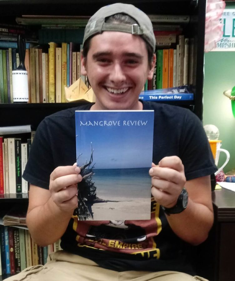 EN Photo by Trinia Oliver // Zack de Armond holding a copy of the most recent issue of Mangrove Review.