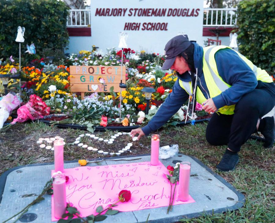 School+crossing+guard+Wendy+Behrend+lights+a+candle+at+a+memorial+outside+Marjory+Stoneman+Douglas+High+School+during+the+one-year+anniversary+of+the+school+shooting%2C+Thursday%2C+Feb.+14%2C+2019%2C+in+Parkland%2C+Fla.+A+year+ago+on+Thursday%2C+14+students+and+three+staff+members+were+killed+when+a+gunman+opened+fire+at+the+high+school.++%28AP+Photo%2FWilfredo+Lee%29