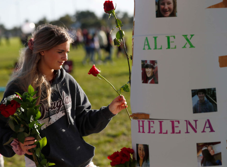 Abbie Elkan, 15, decorates posters of the victims of the Parkland, Fla., shooting, before the start of an interfaith service, Thursday, Feb. 14, 2019, in Parkland, Fla. More than a thousand people gathered at a South Florida park on the anniversary of the Marjory Stoneman Douglas High massacre to honor the 17 victims killed. (AP Photo/Wilfredo Lee)