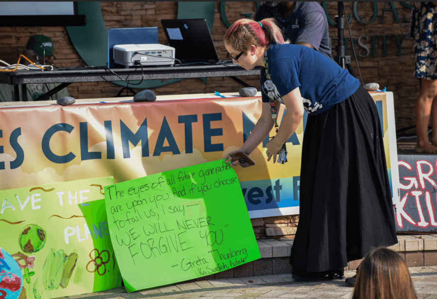 EN Photo by Raphaella Matta. An attendee places a sign on the ground with a quote from Greta Thunburg.